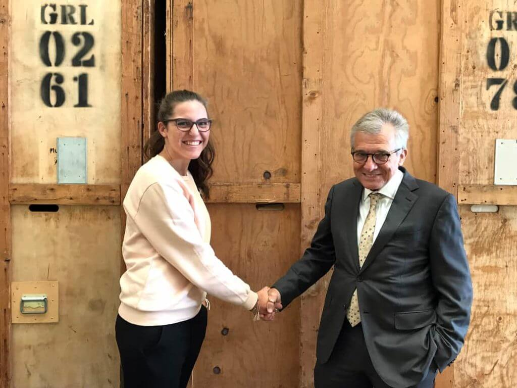 Man In Suit Shaking Hands With Young Woman In Front Of Crates