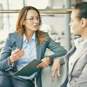 two women talking with clipboard