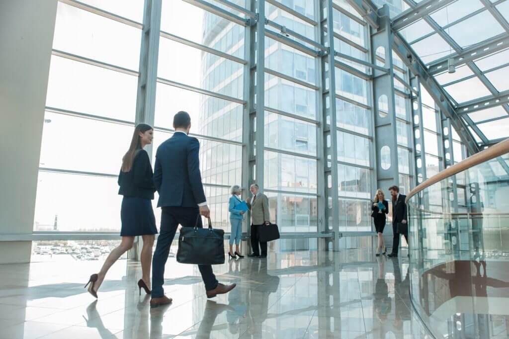 People Walking In Modern Glass Building