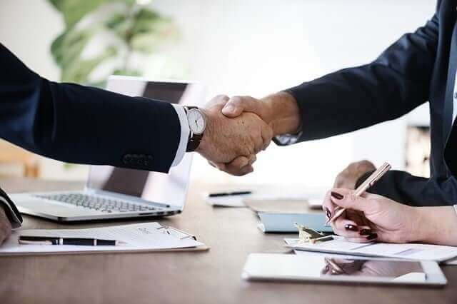 Two people shaking hands in a business meeting.