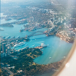 An aerial view from an aeroplane window over Sydney's harbour and green spaces