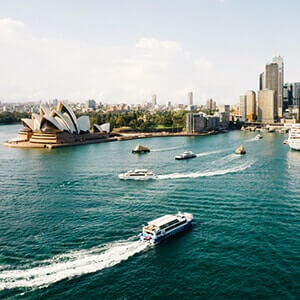 Boats moving around Sydney's Harbour with a view of the city skyline and Opera House..png