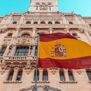 A Spanish flag with a tall Madrid building in the background, in a clear blue-sky day