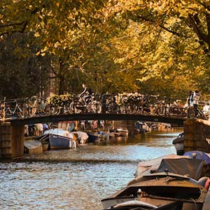 A bridge over one of Amsterdam's canals with autumn leaves and bicycles lining the paths