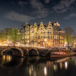 A nighttime shot across an Amsterdam canal picturing a lit bridge and elegant building