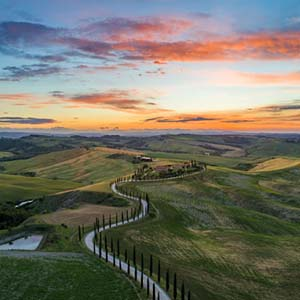 A road winds through the green Tuscany hills as the sun sets on the horizon