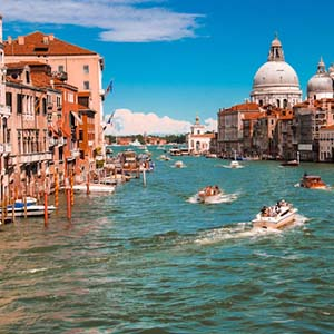 Boats on the waterways of Venice with red-roofed buildings lining the water's edge