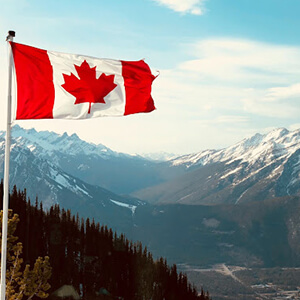 Canadian flag displayed against the Rocky Mountains
