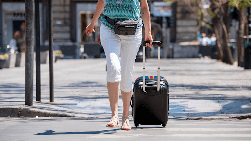 Lady walking out of the airport with her suitcase