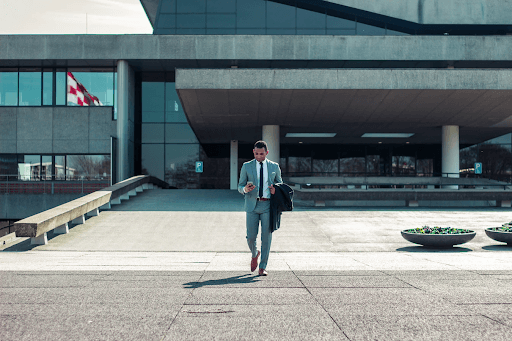 Man Walking Out Of Large Buisness Building