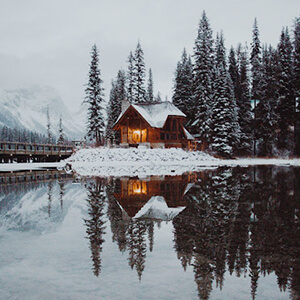 Snowy cabin on a lake scene against a backdrop of Candian mountains