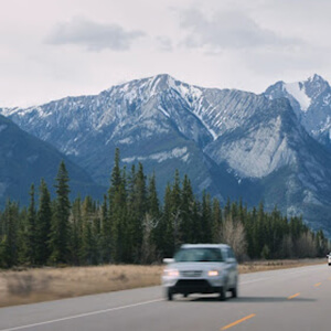 Vehicles driving on open Canadian roads with mountains in the background