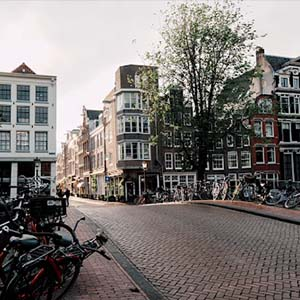 View of a cobbled street in Amsterdam with bicycles lining the fences