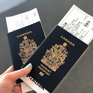 Woman's hand holding two Canadian passports and airline tickets