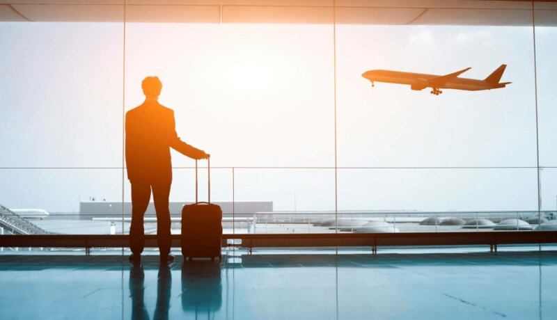 Silhouette of business person in the airport with luggage