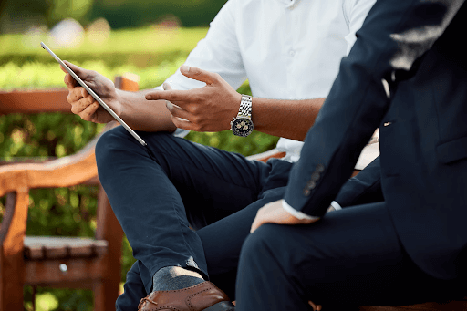 Smartly Dressed Business Men Sitting On A Bench Outside Having A Meeting And Holding A Tablet